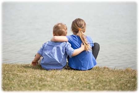 Image of a young brother and sister, from the back, sitting by a lake